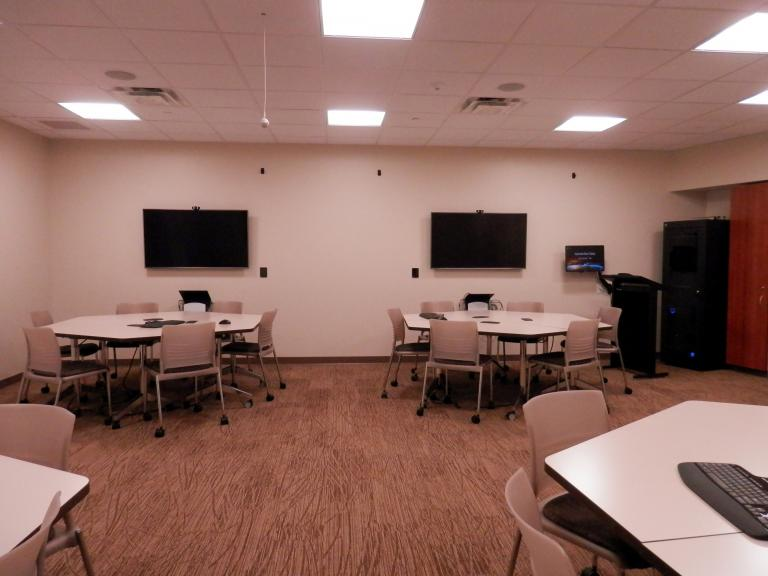 Photo partially reveals the inside of the experimental classroom. There are one ceiling speaker, four 6-seat configurable tables with a monitor on the wall behind each table, one instructor stand and the control closet.