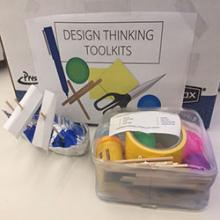 "On a table is a clear, plastic case filled with craft supplies, visibly including duct tape and ping pong balls. Beside the case is a boat made of aluminum foil and paper. In the background is a large cardboard box labeled ""Design Thinking Toolkits."""