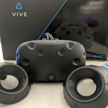 A headset and two controllers of a HTC Vive VR system are placed in front of the packaging box.