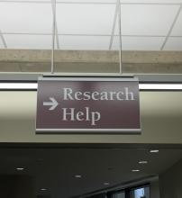 The photo displays a sign hanging down from the ceiling with an right arrow and text Research Help on it.